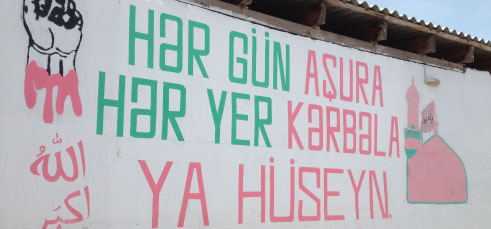 "A painted sign stating ""Every day is Ashura, Every place is Karbala, Ya Hussein"" in Nardaran. Courtesy of the author."